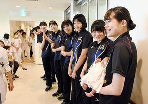 生まれて数日の赤ちゃんを抱っこし、笑顔を見せる久光製薬の比金みなみ選手(手前)=佐賀市の県医療センター好生館