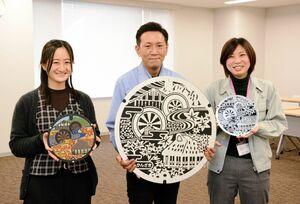 マンホールデザインの壁掛けを制作した浜新硝子の担当者と、神埼市下水道課職員(右)=神埼市役所