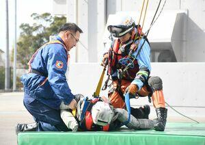 冠水した道路に車が孤立し、車両の上に要救助者がいることを想定した訓練で、救助にあたる隊員=佐賀市の県消防学校