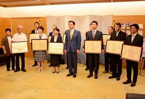 大臣賞を受賞し、山口祥義知事(中央)と記念写真に収まる農家や技術者ら=県庁