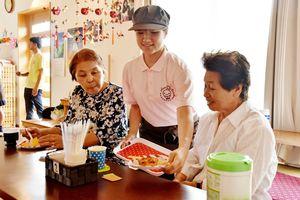 ケーキや飲み物を提供する生徒(中央)と仮説住宅で暮らす住民=熊本県菊池郡大津町