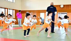 ラグビーボールを手に走り回る子どもたち=佐賀市の諸富文化体育館