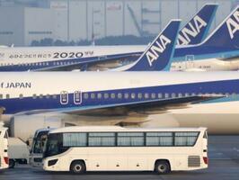 中国・武漢から羽田空港に到着した日本政府のチャーター機第5便に横付けされたバス=17日午前7時2分