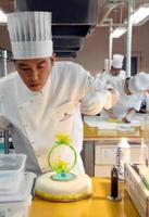 スポンジケーキの上にあめ細工を飾る工芸菓子に挑む参加者=佐賀市の西九州大学佐賀調理製菓専門学校