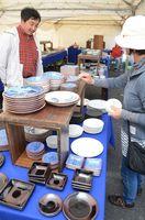 縁取りがとげ状に彫られている「いげ皿」を品定めする来場客=嬉野市嬉野町の肥前吉田焼窯元会館