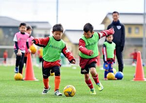 オフェンスとディフェンスに分かれて、ボールを追いかける子どもたち=佐賀市健康運動センター