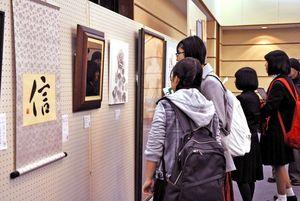 卒業生らの作品に見入る来場者=佐賀市文化会館