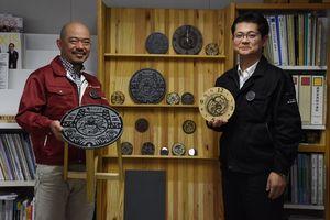 マンホールのふたの図柄を使った掛け時計と椅子を手にする樺島雄大理事長(右)と平田尚士副理事長=佐賀市の諸富デザインセンター