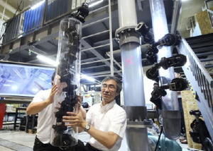 配管内や外側を進むことができるヘビ型ロボット。中央は松野文俊京大教授=29日、京都市
