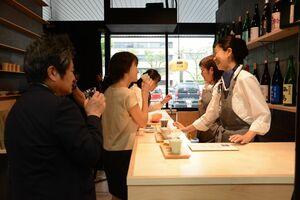 「SAGA BAR」のオープニングセレモニーで一足先に佐賀県産日本酒を楽しむ人たち=佐賀市のJR佐賀駅構内