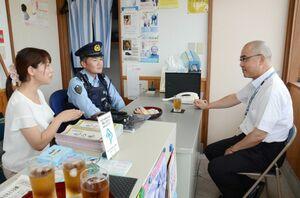 駐在所勤務の警察官と妻をねぎらう県警の三田豪士本部長(右)=唐津市の湊駐在所