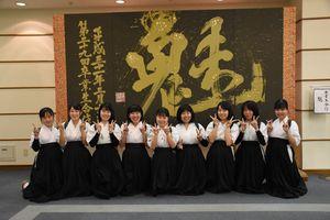 3年生合作の「魅」をバックに、来場を呼び掛ける佐賀北高の生徒たち=佐賀市文化会館