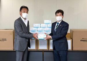 みやき町にマスクを寄贈した栗山建設の栗山清規社長(左)=同町庁舎