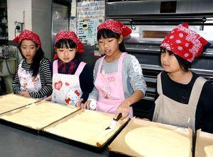 小学生にさまざまな職業を体験してもらう「キッズドリーム基山」で、洋菓子店でロールケーキの生地を平平らに伸ばす仕事に挑戦する小学生たち=基山町の「あびによん」