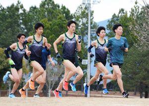 起伏のあるコースを使ってインターバル走を行う選手ら=鹿島市陸上競技場