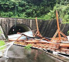 台風7号の強風で道路脇の丸太小屋のトタン屋根が崩れ、国道323号をふさいだ=佐賀市富士町古湯(ツイッターより)