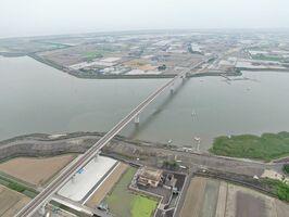 7月24日の開通が発表された有明海沿岸道路の芦刈南-福富ICに架かる六角川大橋。手前が芦刈側(ドローンで空撮)
