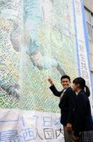 自分が描かれたモザイクアートを見上げる高志館高3年の田川亨介さん(左)