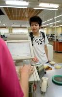 学生食堂のレジでミールカードをかざし、会計を済ませる岳尾友樹さん=佐賀市の佐賀大学本庄キャンパス