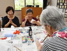 風鈴に絵をつける参加者たち=県総合保健会館
