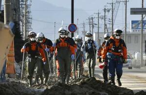 千曲川の堤防決壊で浸水した地域で、捜索活動に向かう消防隊員ら=16日午前7時48分、長野市