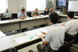 九州電力の担当者(手前)の説明を聞く市民団体のメンバー=東松浦郡玄海町の玄海エネルギーパーク