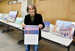 自身の風景画作品を収めたカレンダーを手にする大石琢身さん。鳥栖市と基山町の小中学校に寄贈された=鳥栖市役所