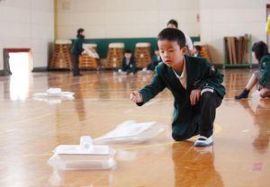 ホーバークラフトを床に走らせる児童
