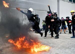 香港の政府本部庁舎に向かって、火炎瓶を投げる若者=15日(共同)