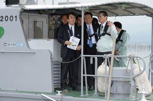 船上で徳永重昭組合長(右)の説明に耳を傾ける斎藤農相(左)。中央は山口知事=鹿島市七浦沖のノリ漁場