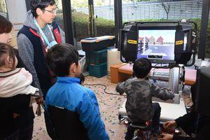 自転車のシミュレーターを使い、自転車の正しい乗り方を学ぶ子どもたち=佐賀市の佐賀市文化会館