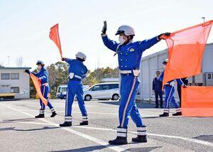 交通規制時の旗振りを訓練する県警高速隊の新隊員=佐賀市大和町の西日本高速道路九州支社佐賀高速道路事務所