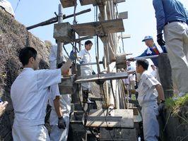 水車の取り付けを行う建築科の生徒たち=唐津市相知町の町切地区