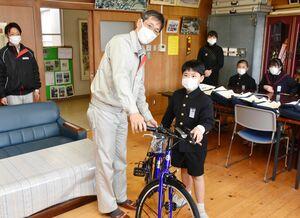八巻一彦工場長から自転車を贈られた「工場長賞」の長谷川翔一君=鳥栖市の麓小