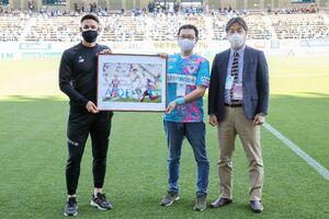 4月の月間MVPに選ばれ、記念のパネルを受け取る酒井宣福(左、サガン・ドリームス提供)