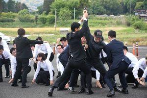 訓練で、聴衆の中で発砲をした男を素早く取り押さえる警護員=佐賀市の運転免許試験場
