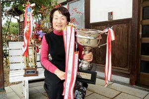 グランドチャンピオンのカップを手にする福川美代子さん=伊万里市黒川町の自宅