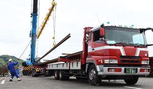 嬉野市の今寺軌道基地へ輸送するためにトレーラーに積載される長さ25メートルのレール=佐世保市
