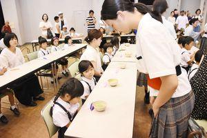 子どもたちはもてなしたり、もてなされたり。高校生からお茶をいただく園児たち=唐津市のアルピノ
