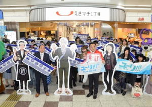 イベントのスタートを記念し、アニメ「ユーリ!!! on ICE」の等身大パネルと一緒に写真に納まるファンたち=JR唐津駅構内