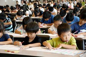 そろばんをはじくように指を動かして計算し、答えを書き込む子どもたち=佐賀市の佐賀駅北館