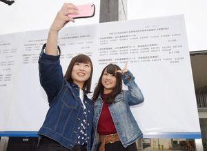 掲示板前で友人と記念撮影をする合格者(右)=佐賀市の佐賀大学本庄キャンパス