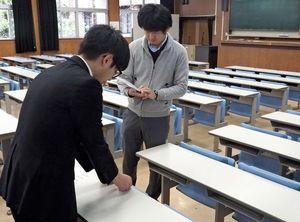 受験番号を読み上げ確認しながら、座席シールを貼る大学職員=佐賀大学本庄キャンパス