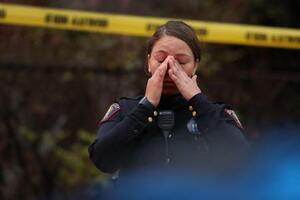 10日、発砲事件の現場で、顔を手で覆う警察官=米ニュージャージー州ジャージーシティー(ゲッティ=共同)