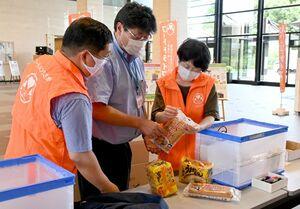 フードドライブで提供された食品を受け取るフードバンクさがの関係者=佐賀市の佐賀県庁