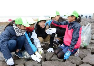 岩の間からゴミを拾い上げるこどもラムサール観察隊=鹿島市の肥前鹿島干潟
