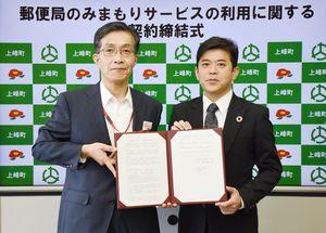 高齢者見守りサービスで契約を締結した日本郵便九州支社の出西信治支社長(左)と上峰町の武広勇平町長=町役場