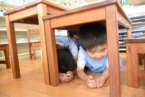 机の下に入り身を守る園児たち=唐津市山下町の唐津カトリック幼稚園