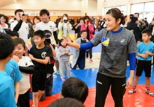 子どもたちと笑顔で触れ合う伊調馨選手(右)=鹿島市の鹿島実高
