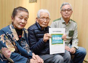 完成した団地史を手にする牟田口さん(中央)ら=佐賀市の佐賀新聞社
